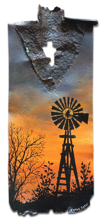 Old rusted spade with windmill in sunset
