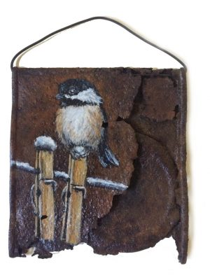 Crushed soup can with chickadee on clothespin